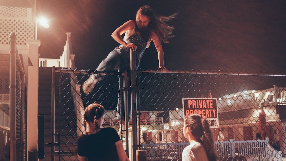 Teenagers climbing a fence at night