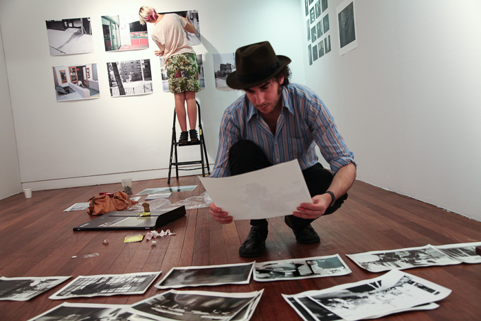 A picture of a photography student crouching on the floor looking at prints